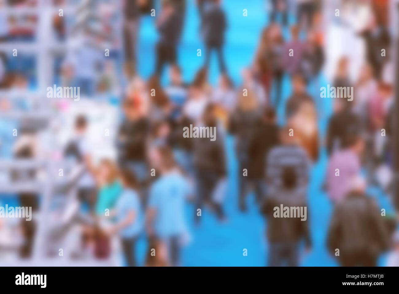 Abstract blurred people attending event in exhibition hall, press conference or celebration party, visitors of indoor - Stock Image