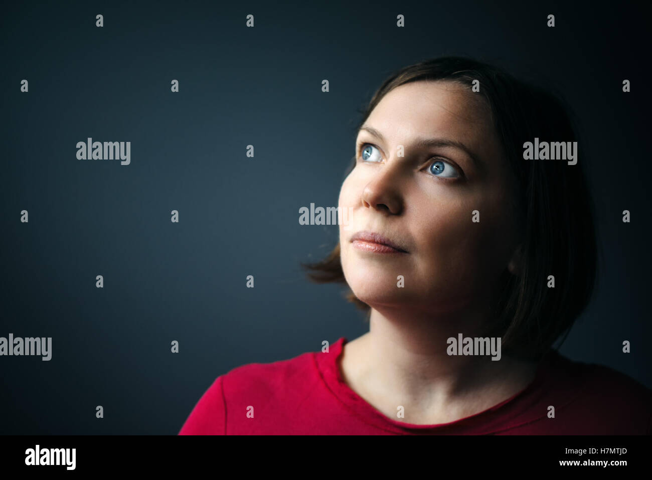 Hope and expectations, beauty portrait of young adult woman looking up to soft light coming from above - Stock Image