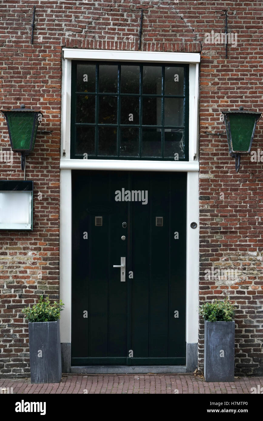 dark green door of an old warped house with red bricks in the Netherlands - Stock Image