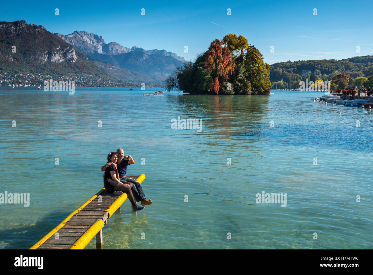 Couple sitting on a pontoon taking a selfie, Lake Annecy, Haute Savoie, France - Stock Image