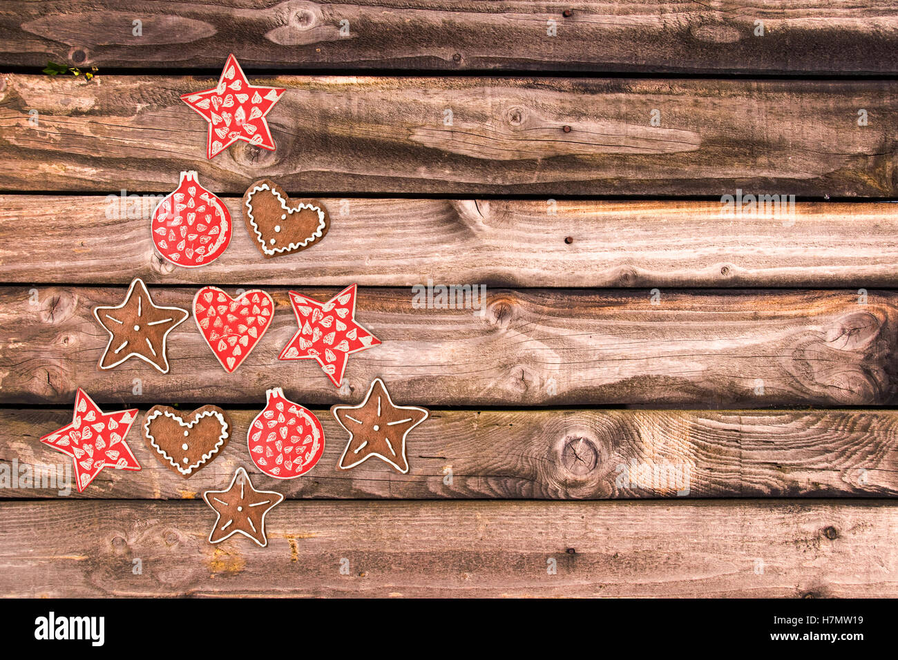 Christmas tree made of wooden rustic ornaments on wooden planks background - Stock Image