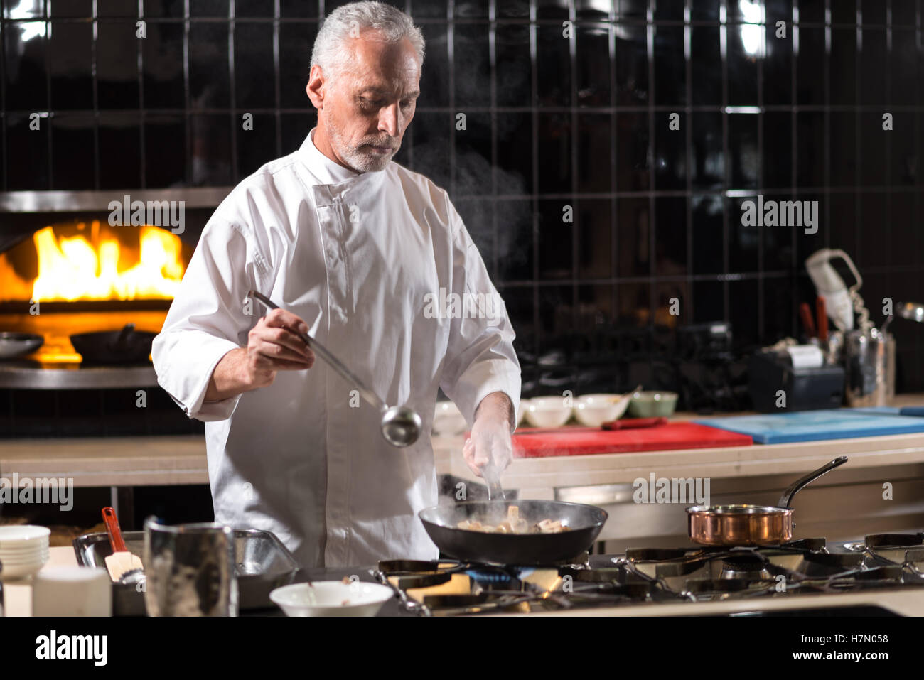 Involved chef mixing mushrooms on the frying pan Stock Photo