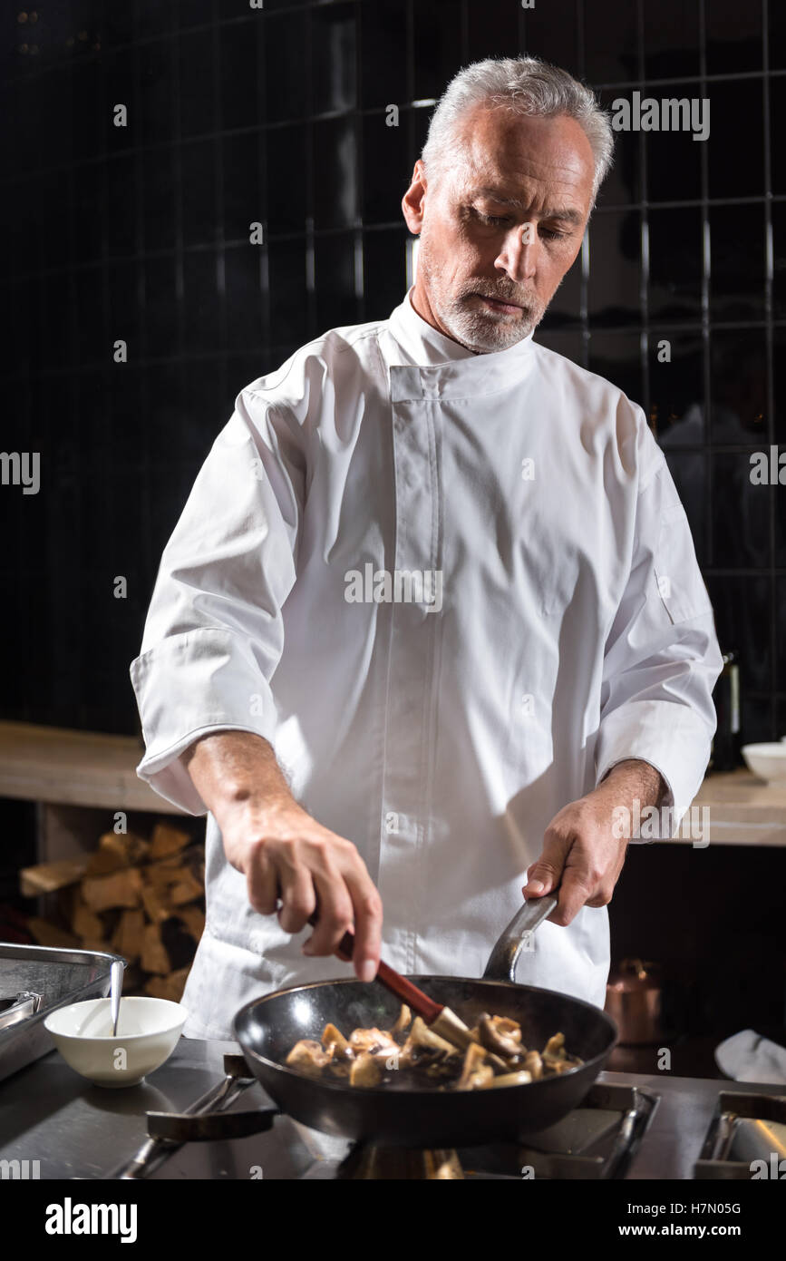 Concentrated chef mixing mushrooms on the frying pan Stock Photo