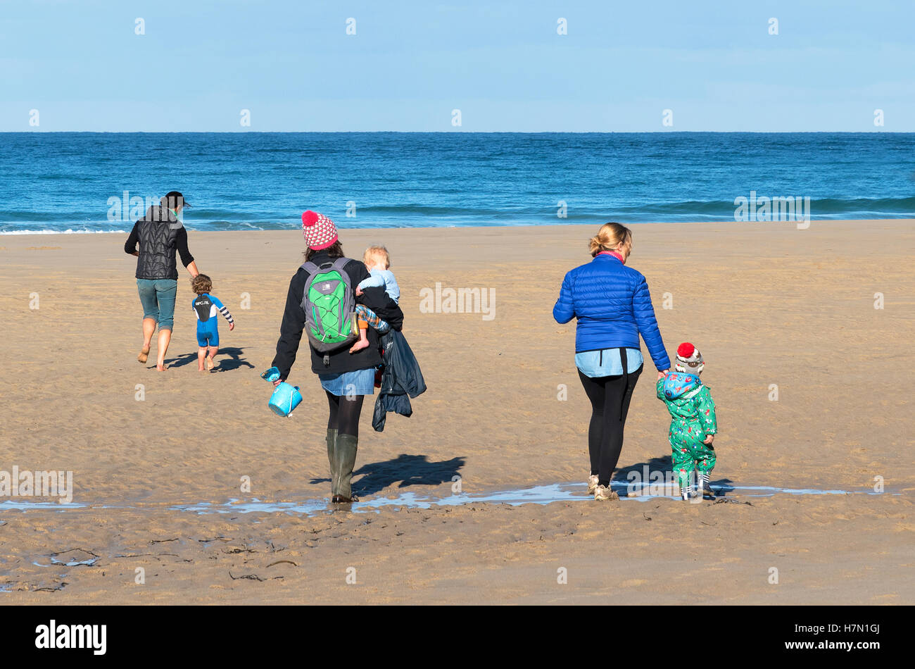 three young mothers on a beach in cornwall, uk, with their children. - Stock Image
