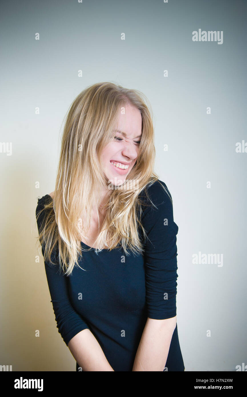 Young blonde woman, smirking with little grimace on white background Stock Photo
