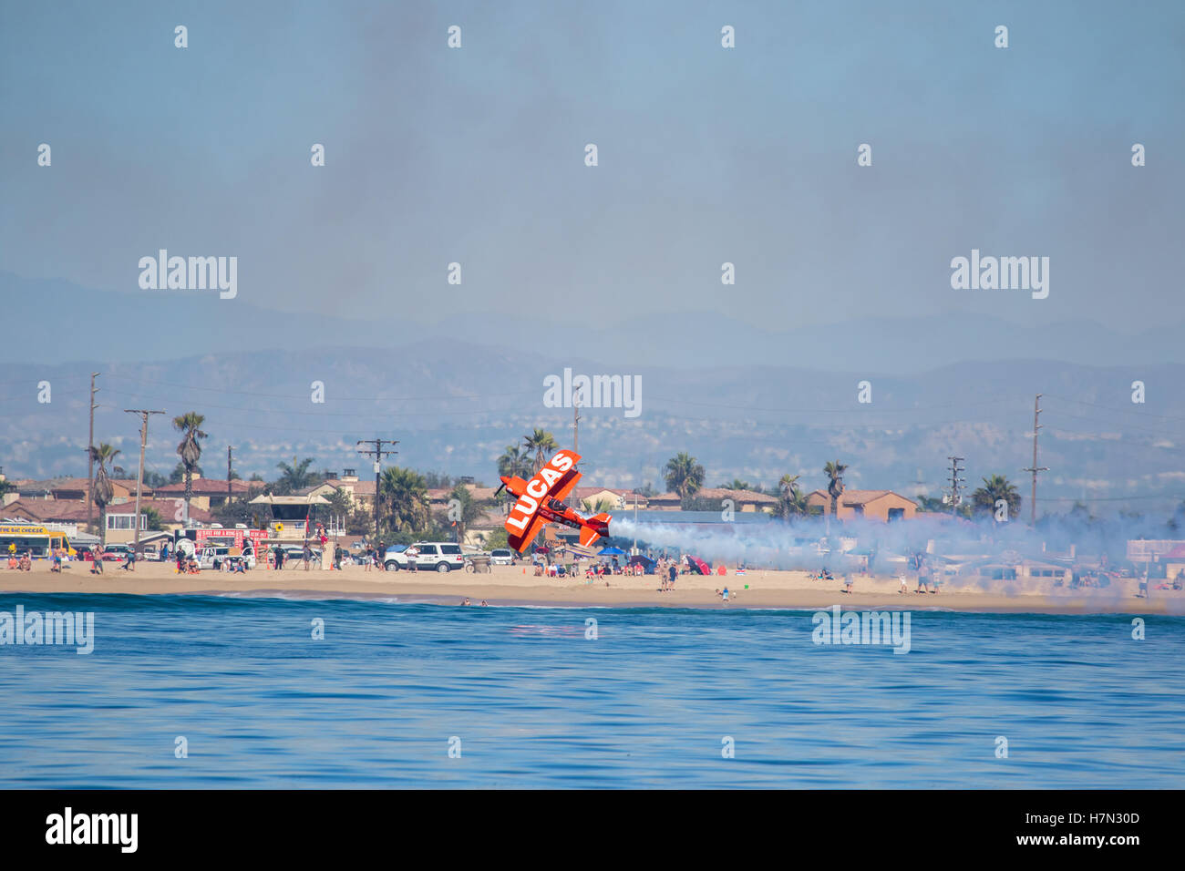Huntington Beach  air show Lucas oil aerobatics stunt plane flies along the waters edge in front of a crowd of spectators - Stock Image