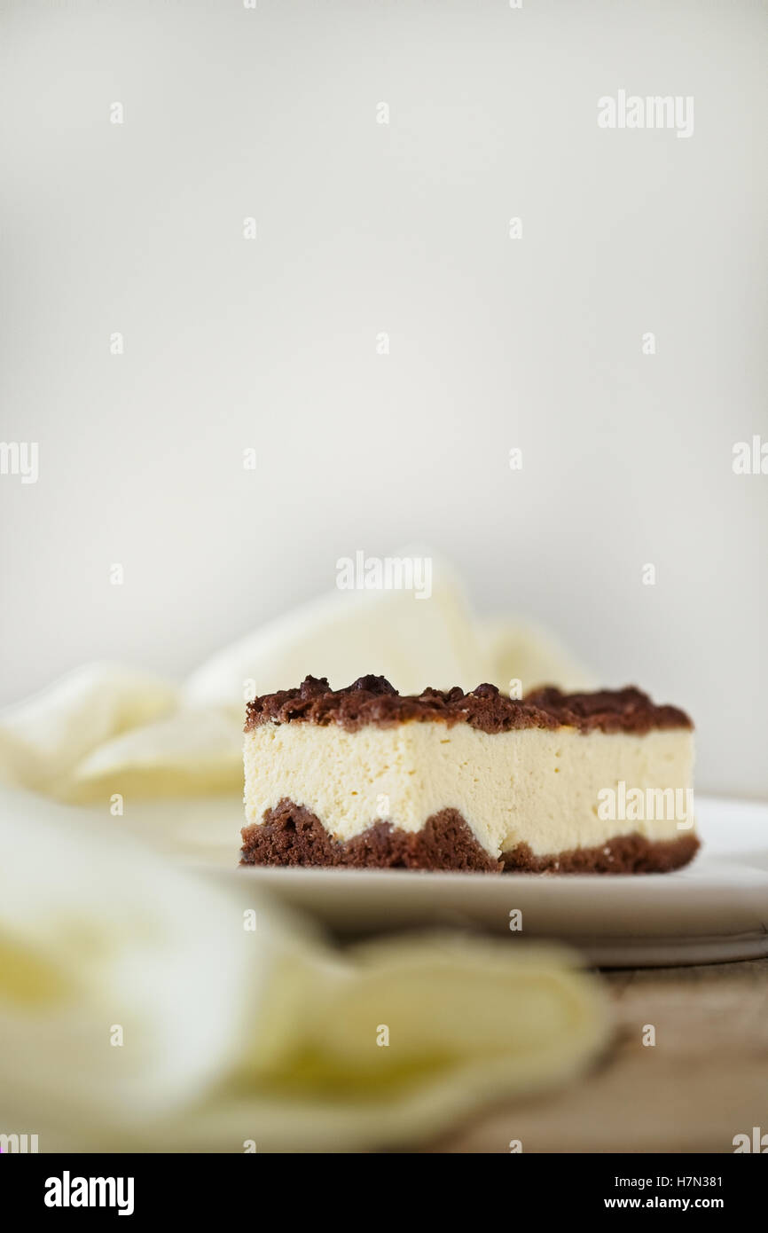 Slice of cheesecake with chocolate shortcrust pastry and chocolate crumble. Yellow linen. Free text space background. - Stock Image