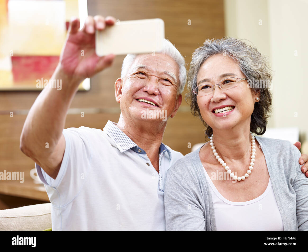 senior asian couple taking a selfie at home using cellphone - Stock Image