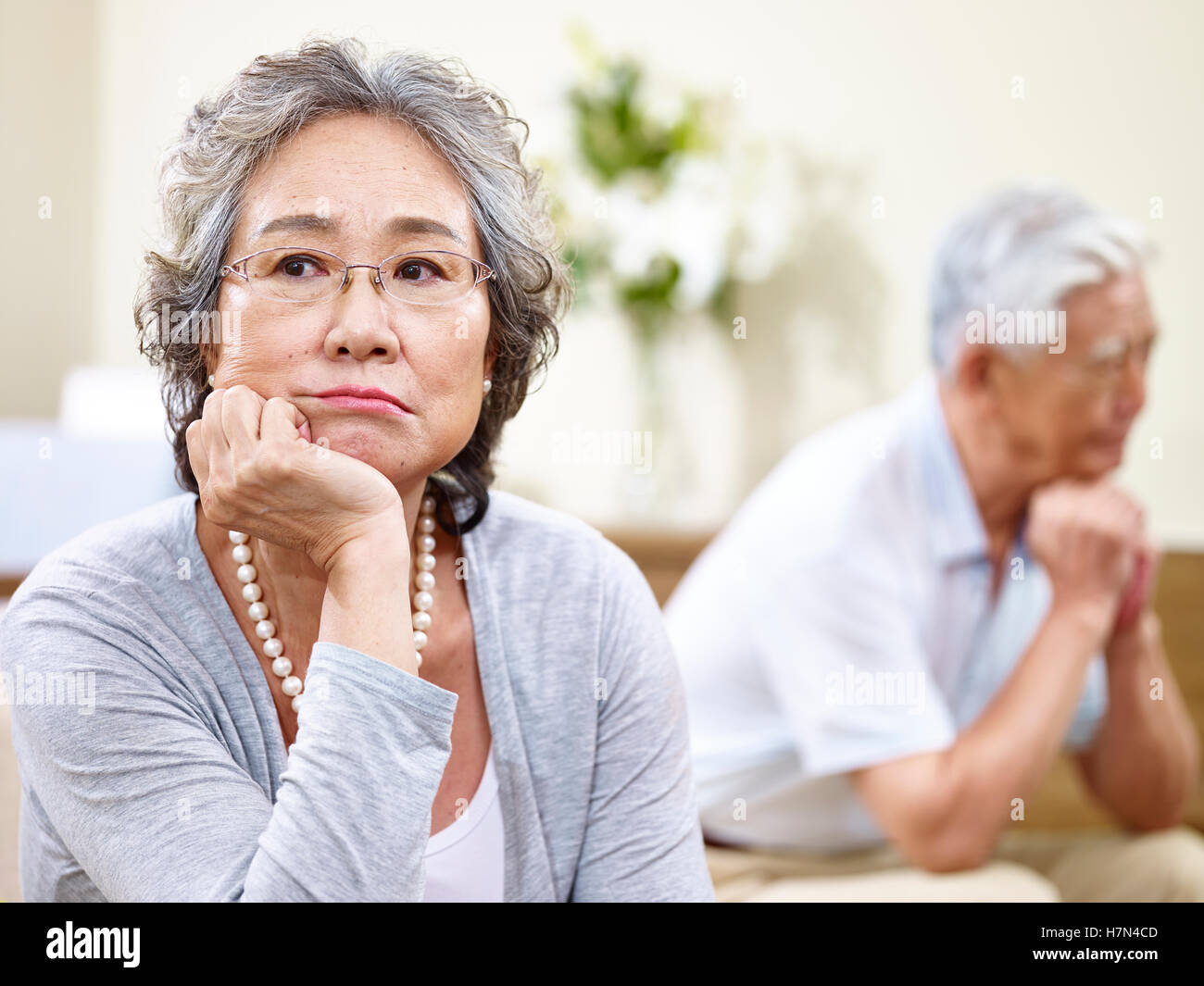 senior asian couple sitting on couch at home, angry at each other - Stock Image