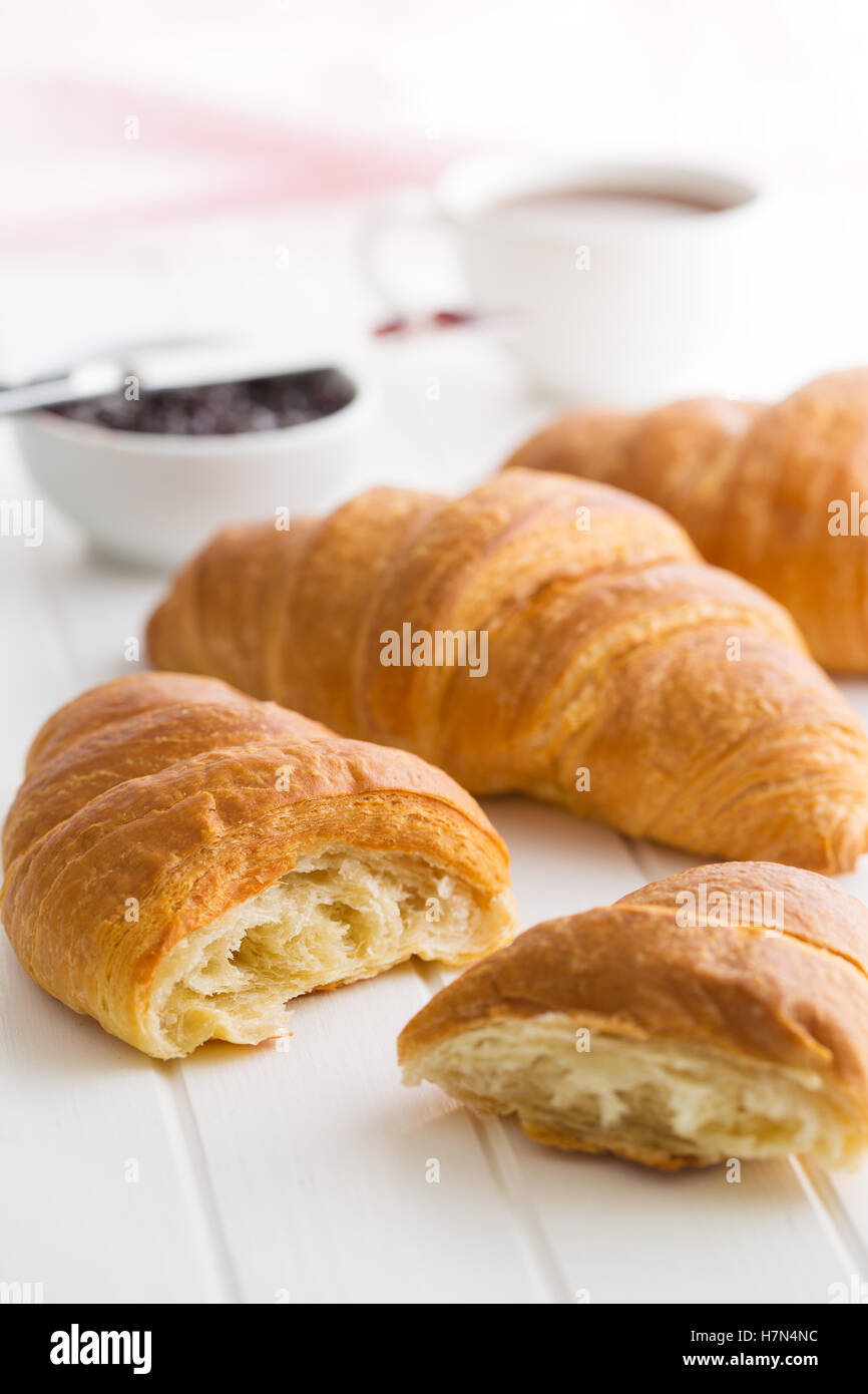 Tasty buttery croissant on white table. - Stock Image