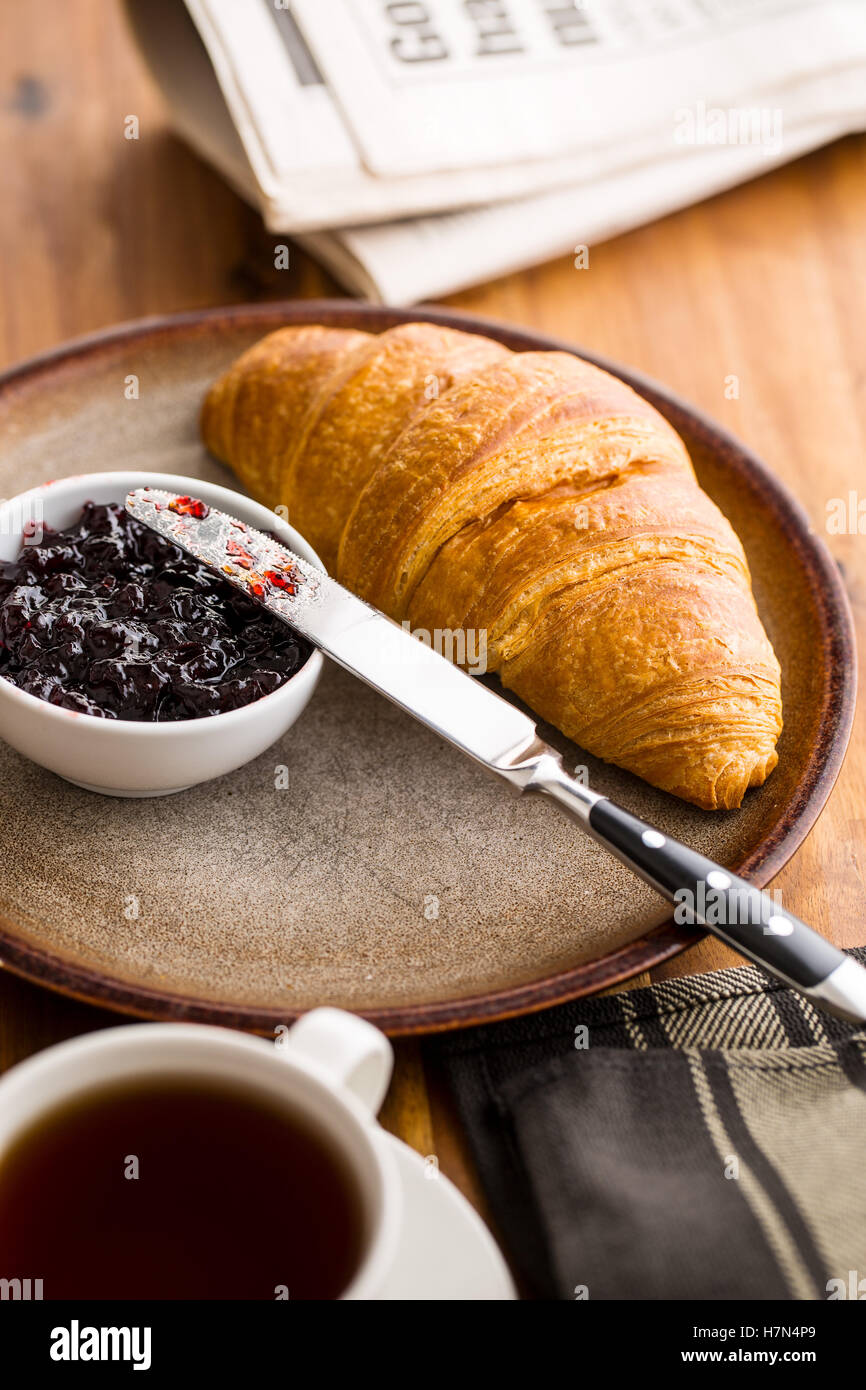 Tasty buttery croissant with jam on plate. - Stock Image