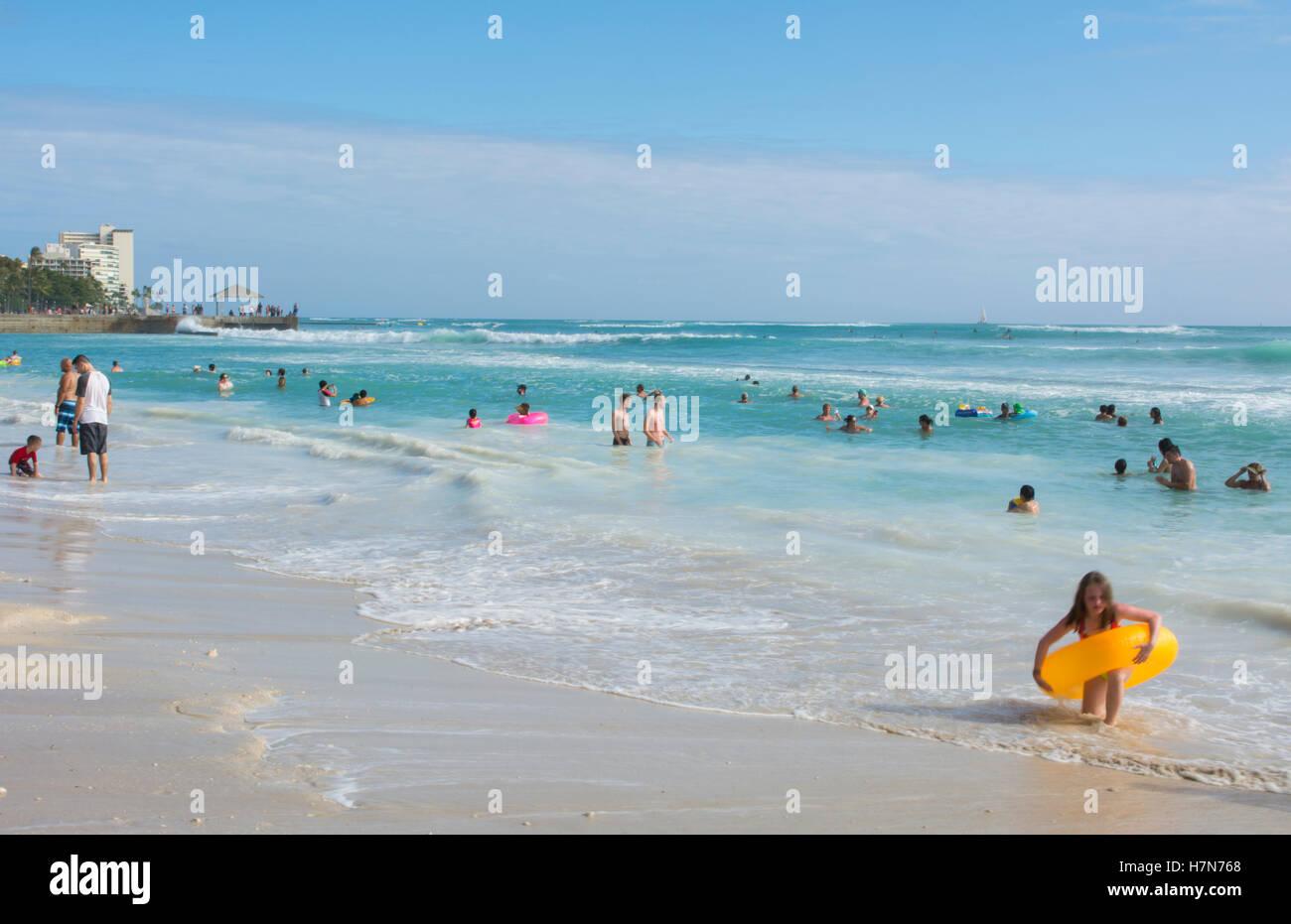 Honolulu Hawaii Oahu Waikiki Beach with tourists on wonderful beach with water and sand - Stock Image