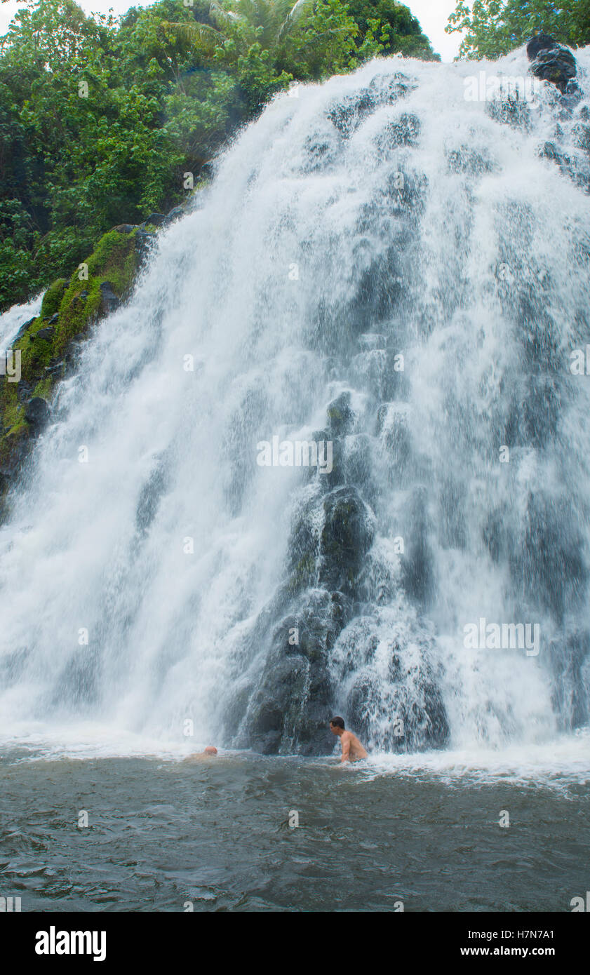 Pohnpei Micronesia Kepirohi  Waterfalll  in forest with water flow with men in water - Stock Image