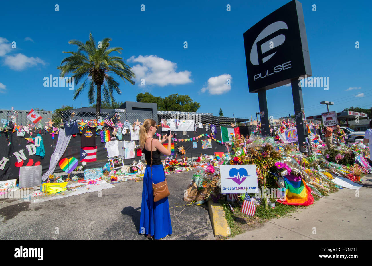 Orlando Florida Pulse night club tragedy shooting memorial at gay bar by terrorist on June 12, 2016, woman taking - Stock Image