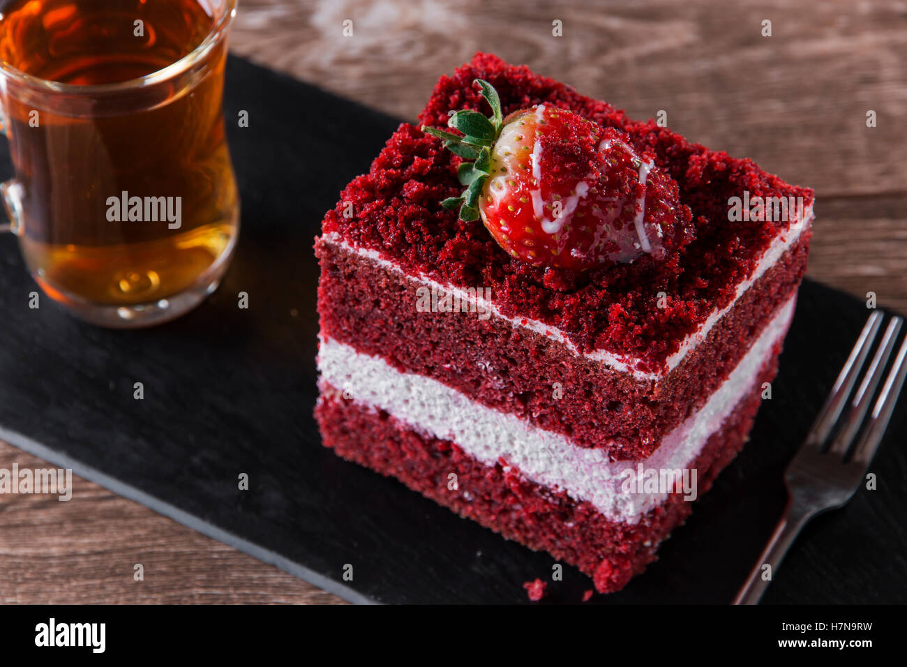 slice of red velvet cake with white frosting is garnished with strawberries close up - Stock Image