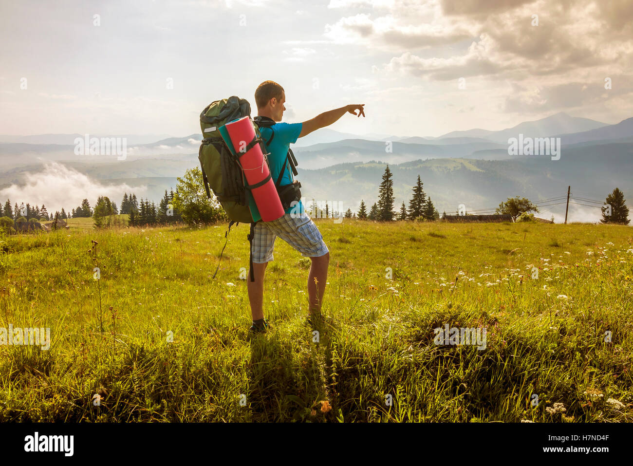 Hiker with a backpack standing in mountains Stock Photo