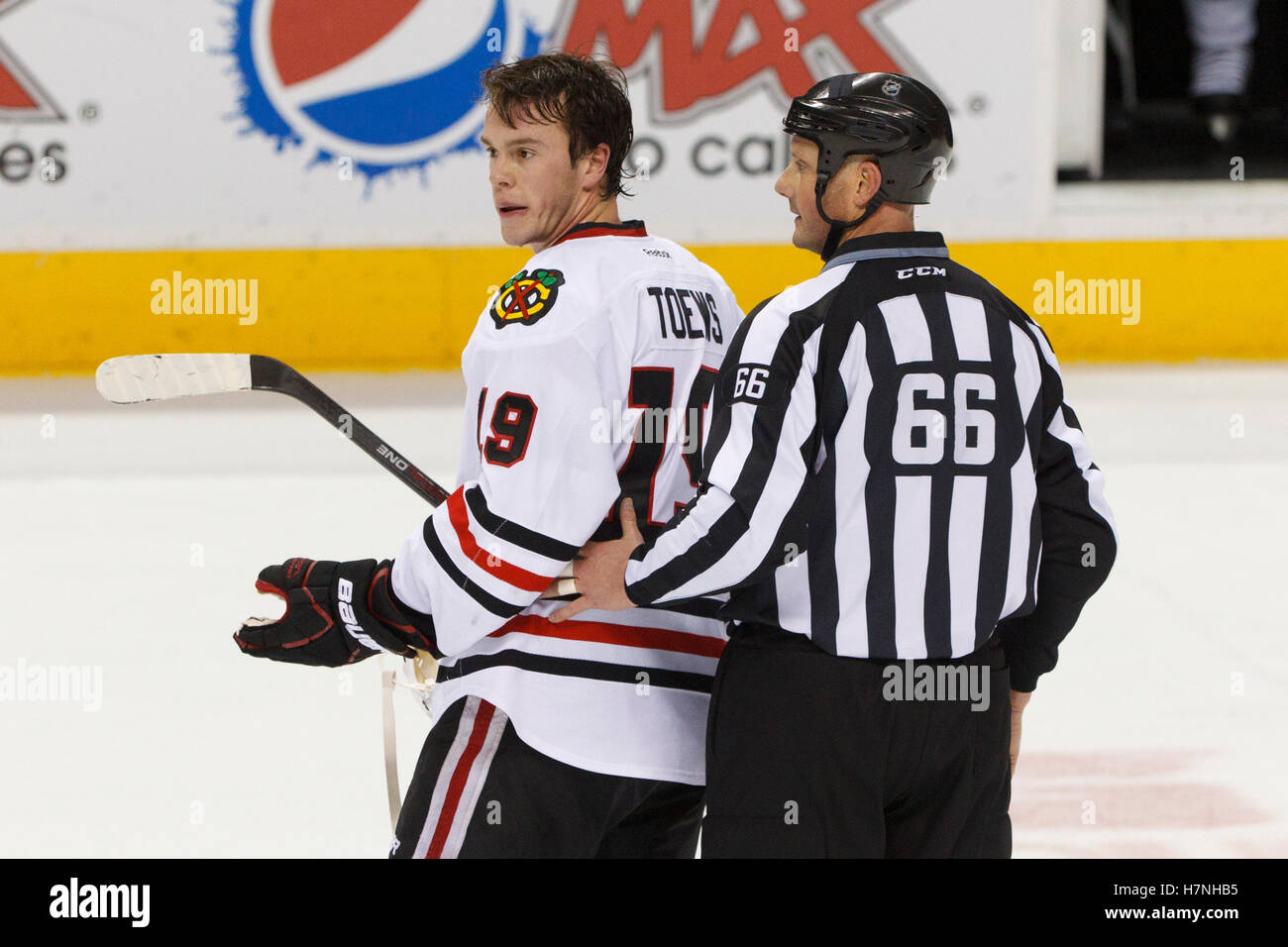 Feb 10, 2012; San Jose, CA, USA; Chicago Blackhawks center Jonathan Toews (19) is escorted by NHL linesman Darren - Stock Image