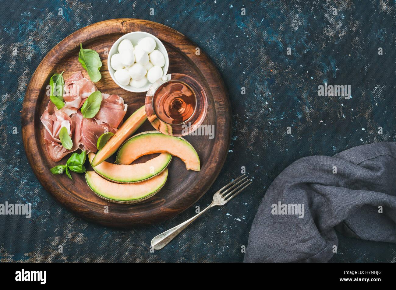 Prosciutto, cantaloupe melon, mozzarella and glass of rose wine - Stock Image