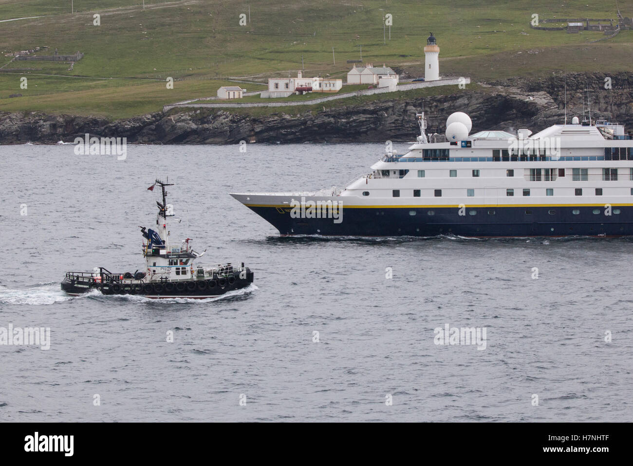 Pilot ship escorts National Geographic Orion in Shetland waters near Lerwick, passing Bressay lighthouse, Kirkabister - Stock Image
