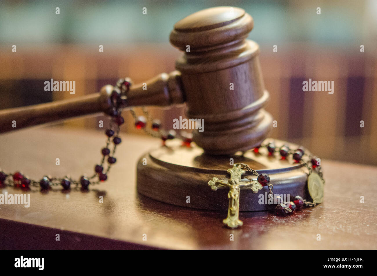 Church and State concept photograph, Gavel with Rosary Beads in Courtroom with jury seats in the background Stock Photo