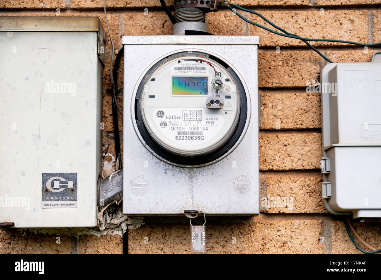 An electric meter attached to the back of a brick home in Oklahoma, USA. - Stock Image