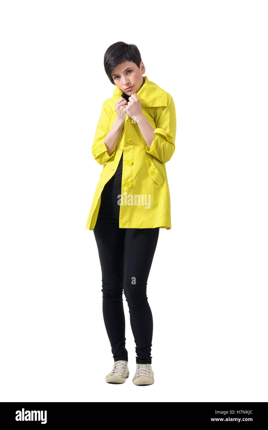 Young short hair brunette freezing covering neck with yellow rain coat. Full body length portrait isolated over - Stock Image