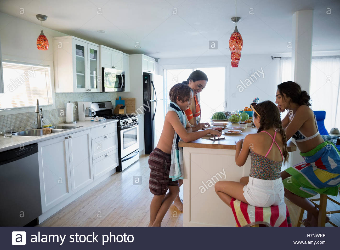 Family in bathing suits eating at kitchen island - Stock Image