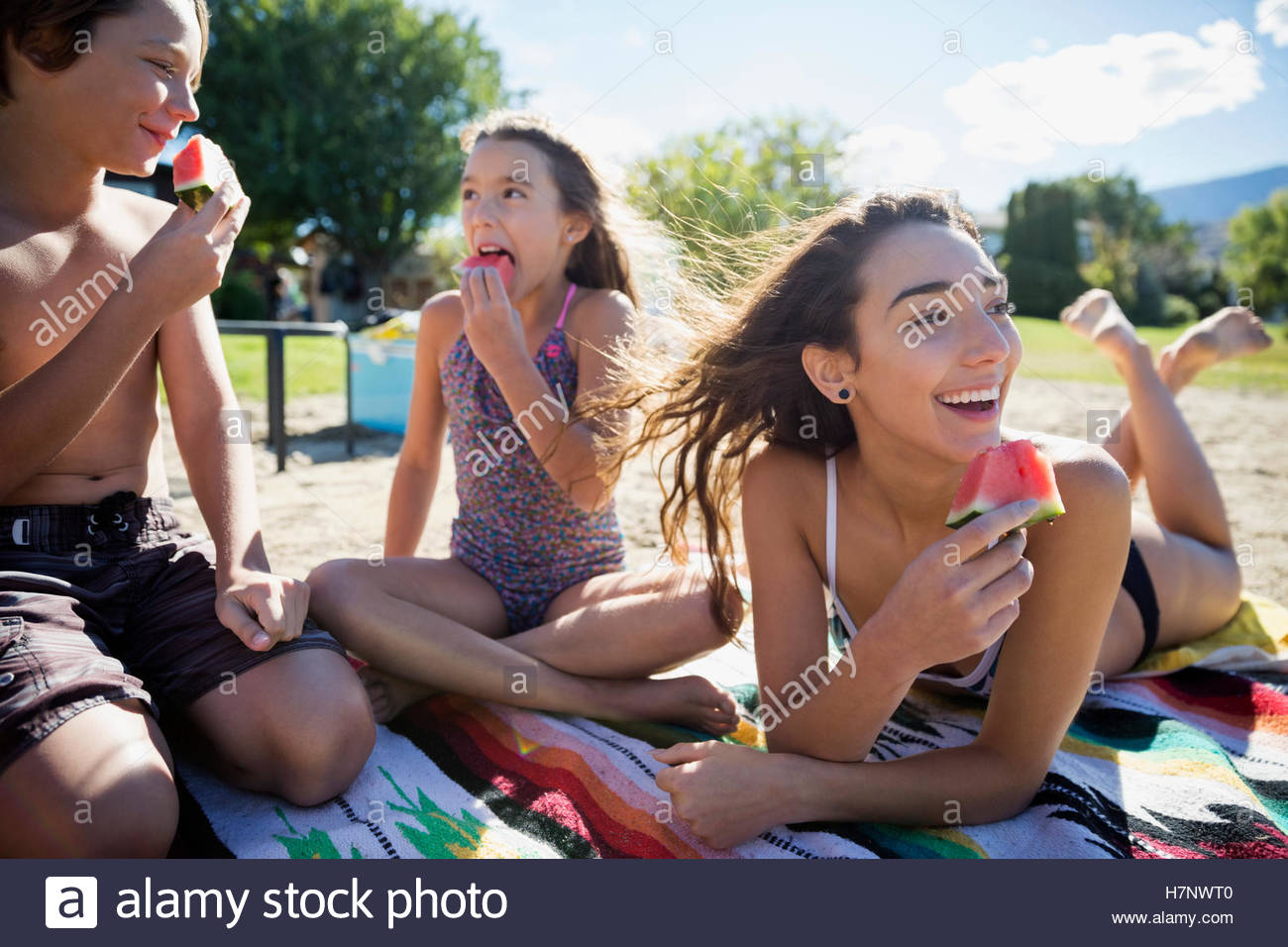 Brother and sisters eating watermelon on sunny summer beach - Stock Image