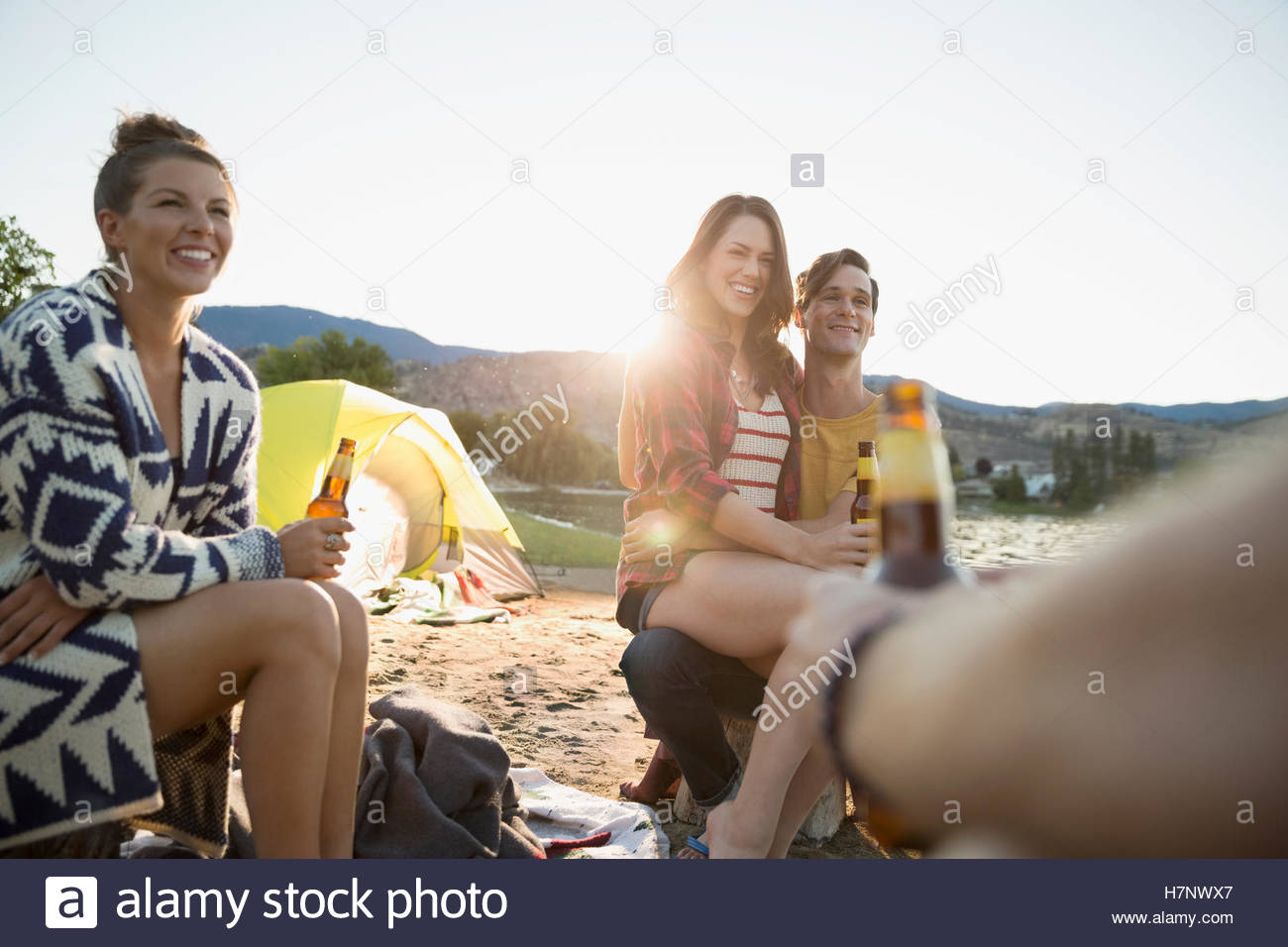 Young friends drinking beer hanging out on summer beach campsite - Stock Image