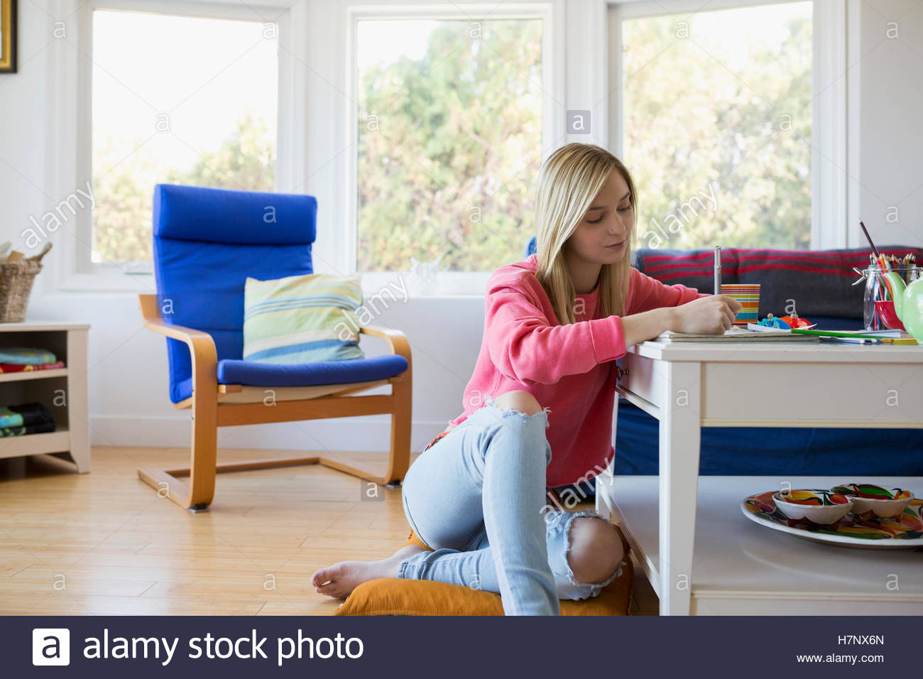 Young woman writing in notebook on coffee table - Stock Image