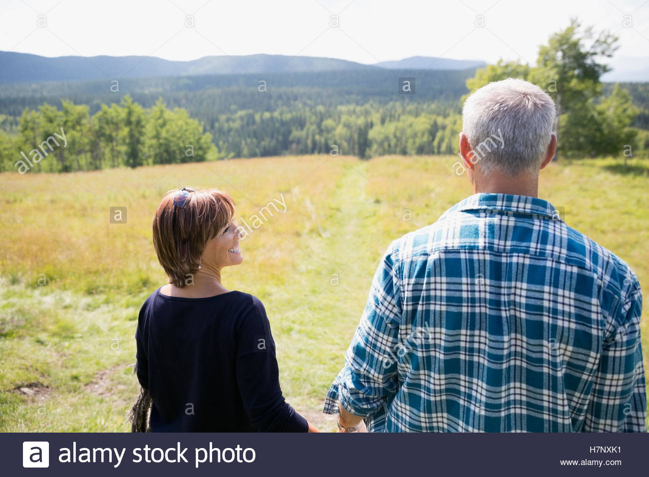 Mature couple walking in sunny remote rural field Stock Photo