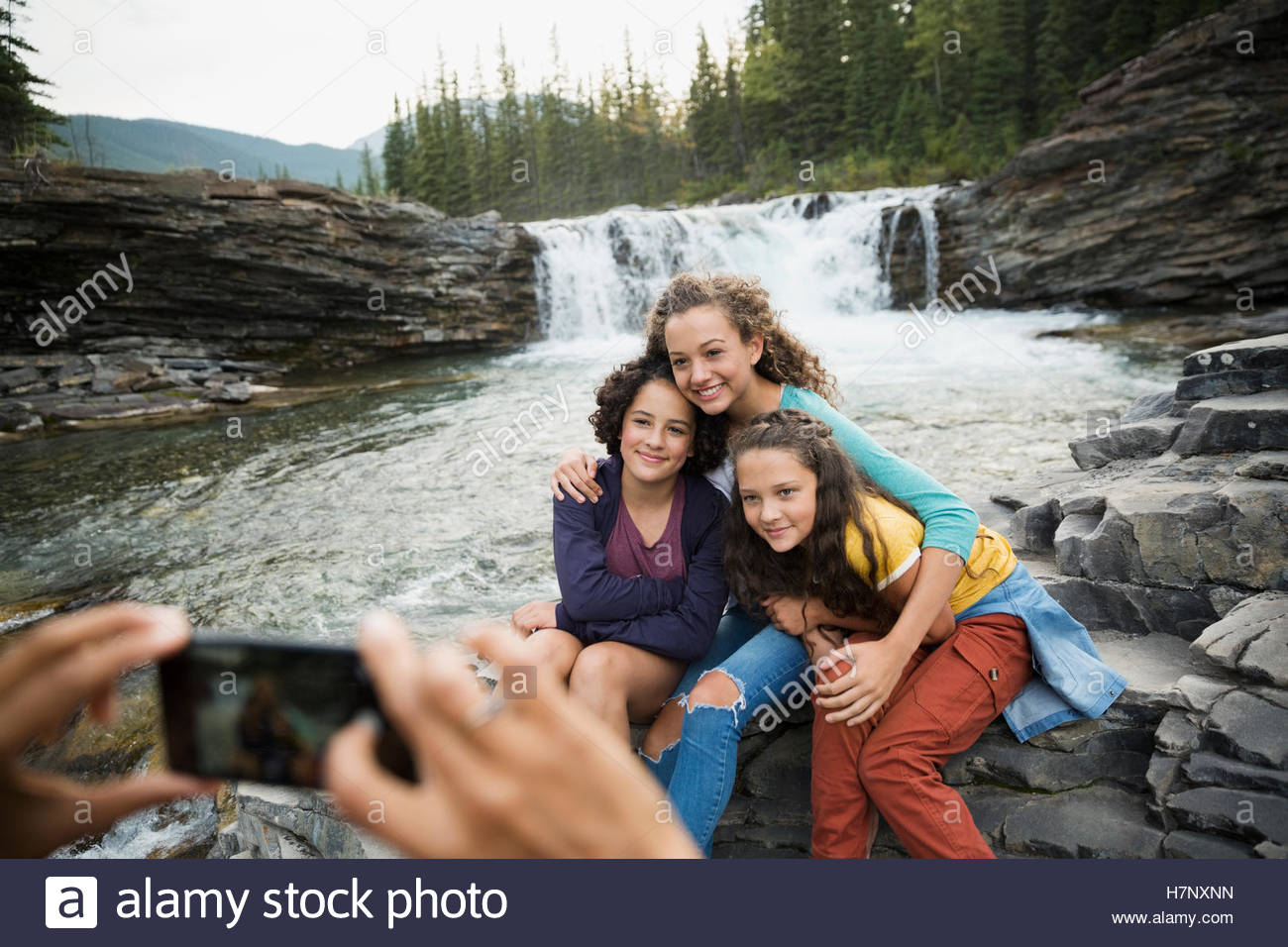 Sisters being photographed by mother at waterfall Stock Photo