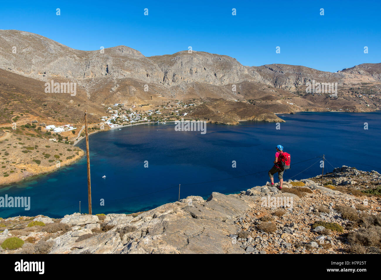 Female walker with red rucksack against sea, Beach blue sea and mountains, Emborios Bay, Kalymnos - Stock Image