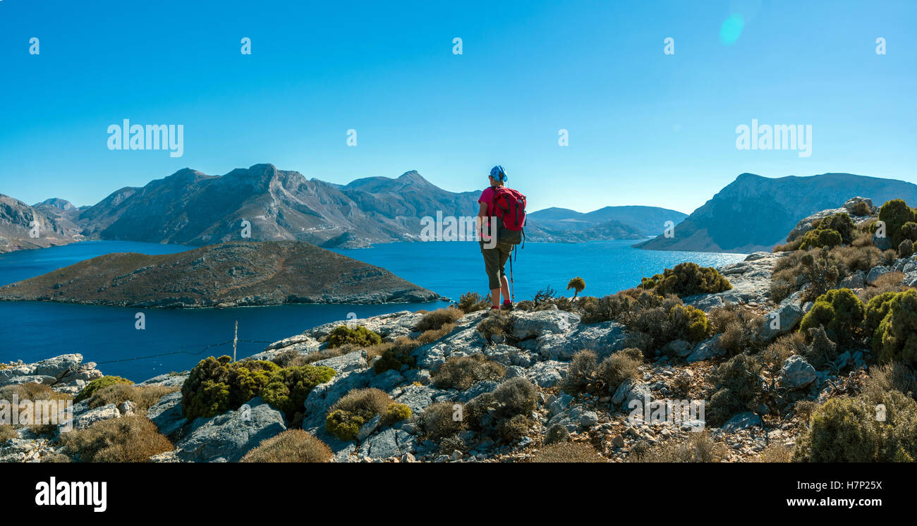 Female figure in red looking out over sea and islands, with blue sky, Emborios Bay, Kalymnos - Stock Image