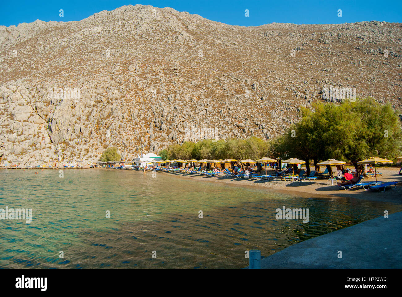 Beach at Saint Nicholas bay on symi with umbrellas, and sun loungers Stock Photo
