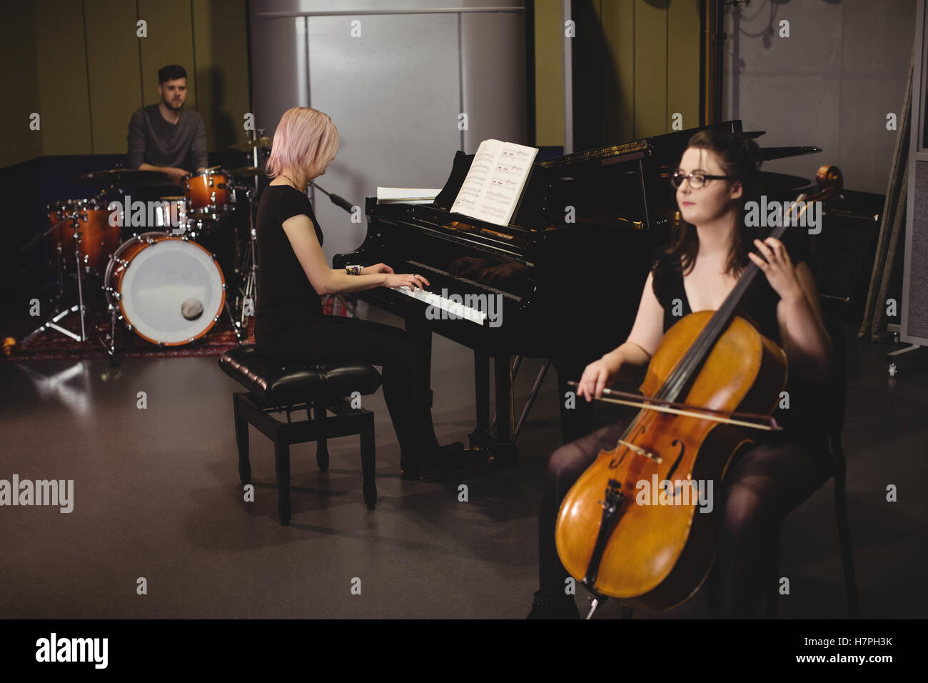 Group of students playing double bass, drum set and piano - Stock Image