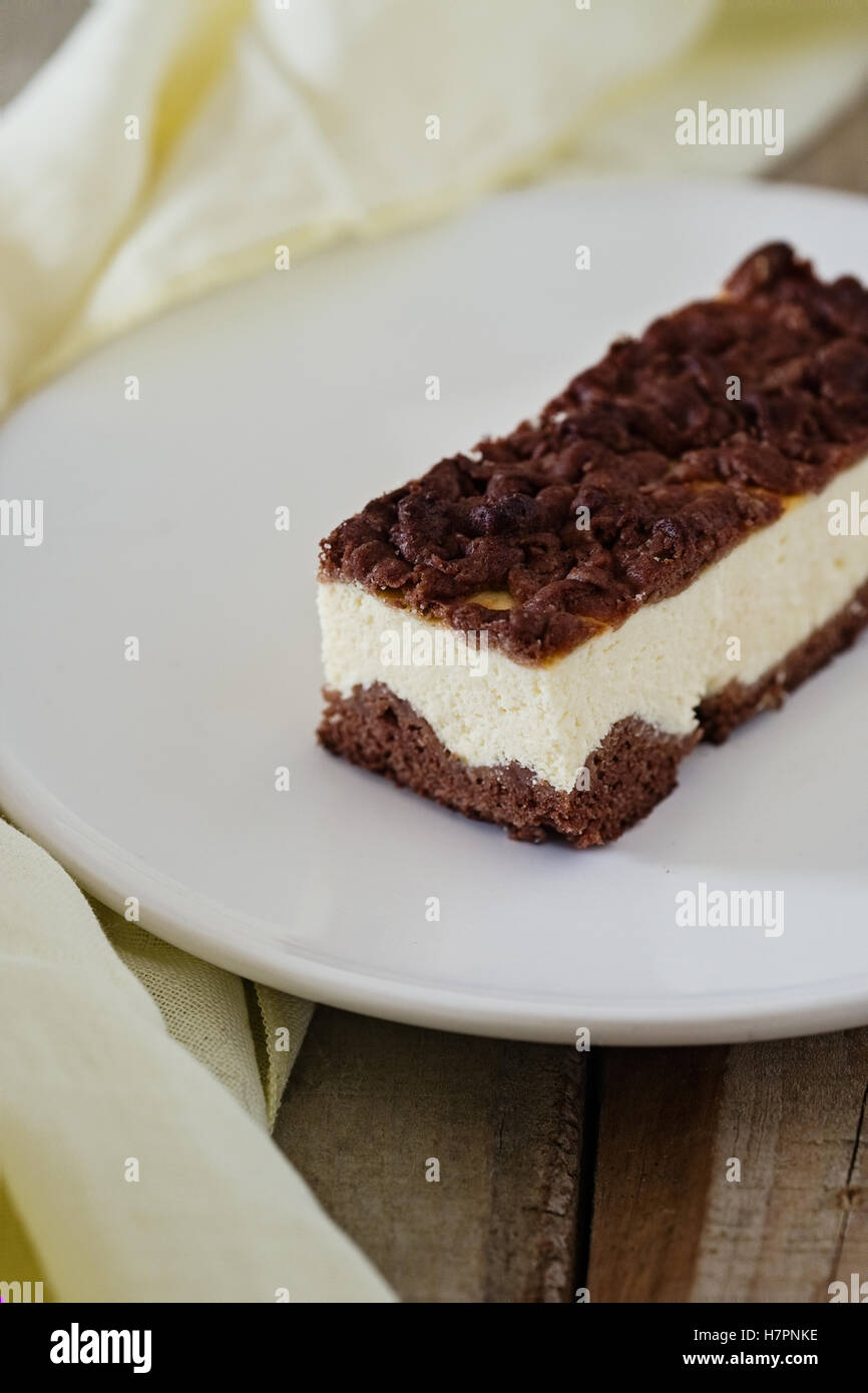 Slice of cheesecake with chocolate shortcrust pastry and chocolate crumble. Wooden background - Stock Image