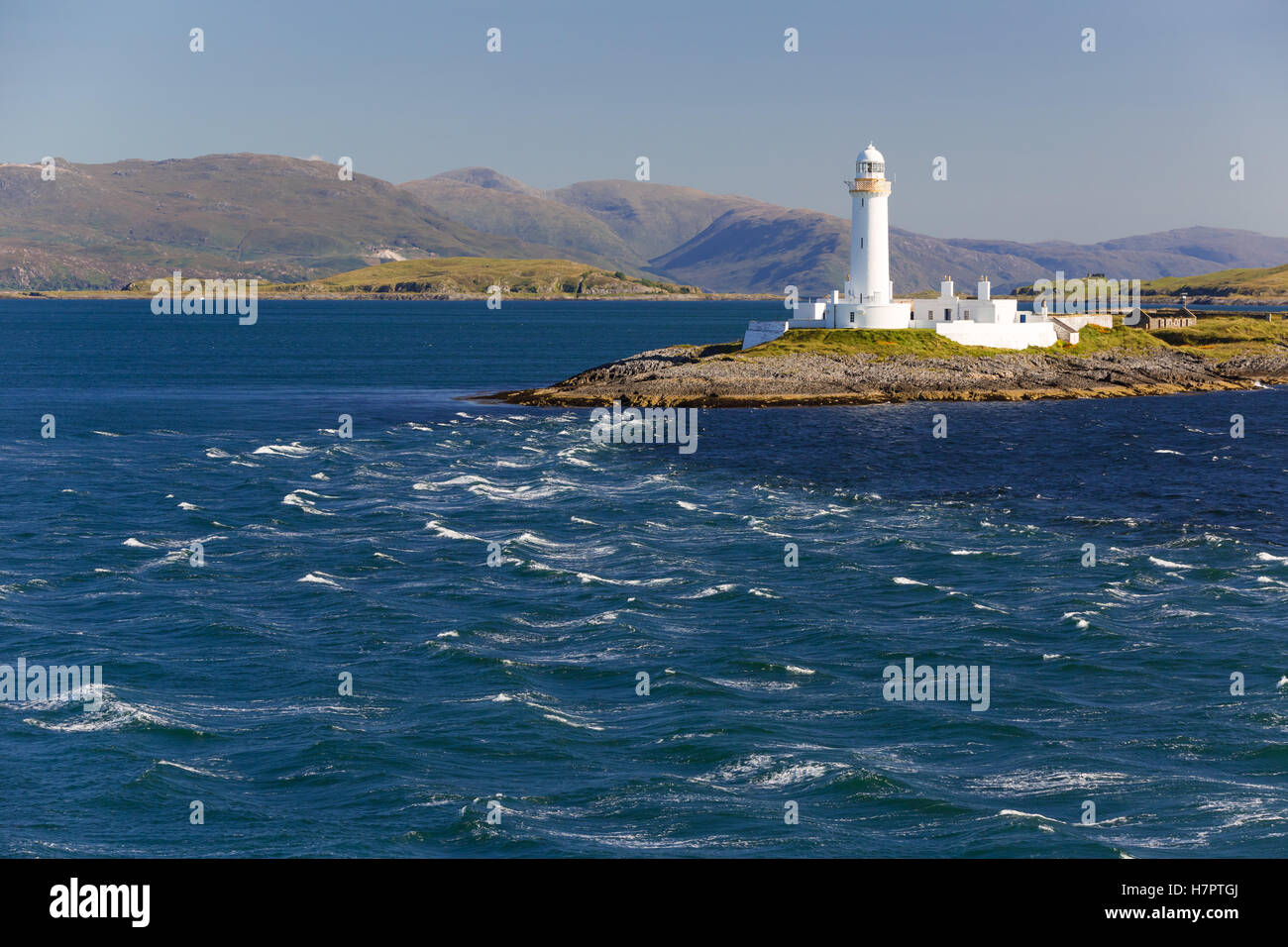 Eilean Musdile lighthouse, southern tip of island of Lismore, Firth of Lorn. Shot from ferry Oban - Isle of Mull. - Stock Image