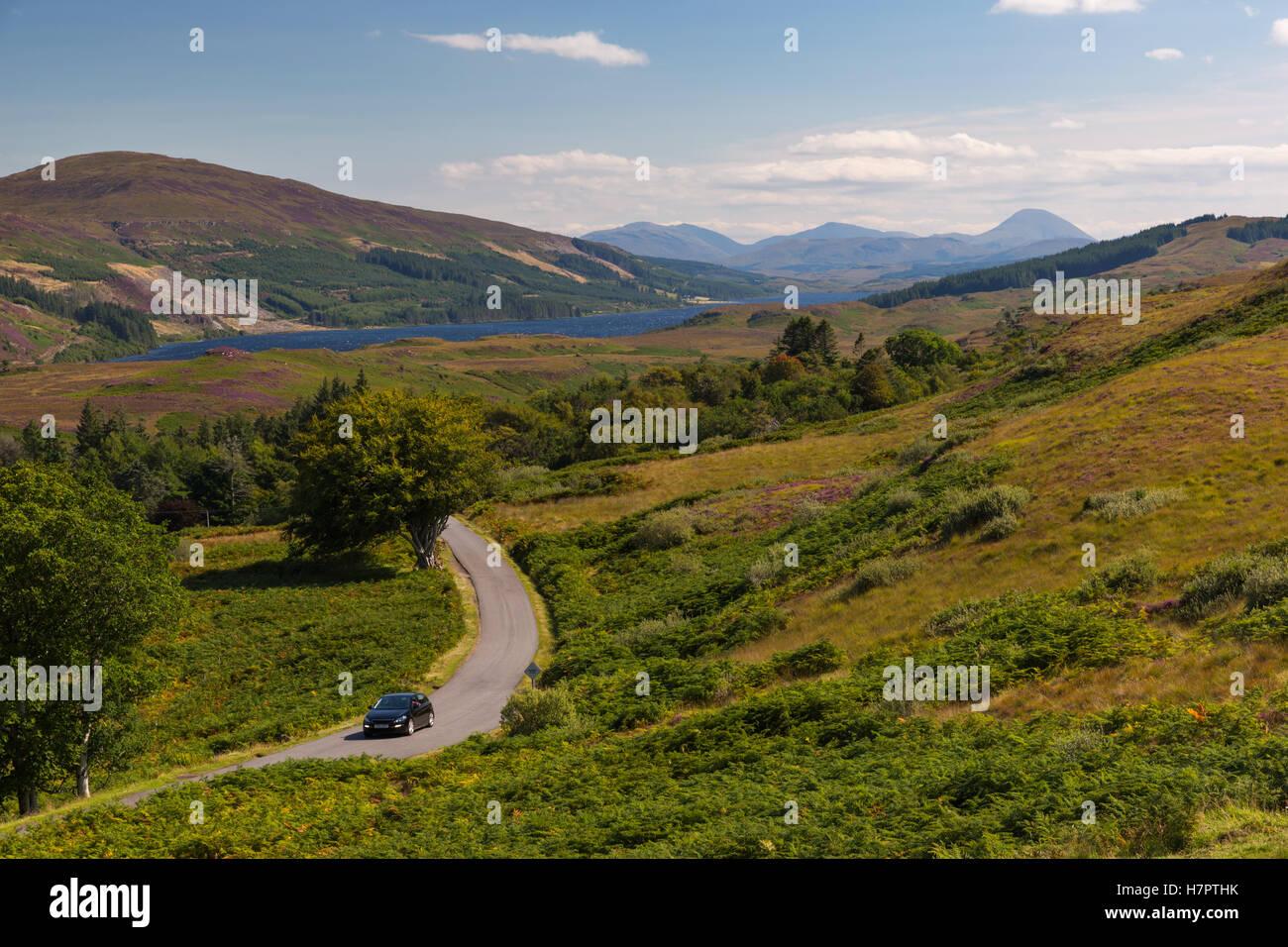 Country road, car cruising Isle of Mull. Highlands, Scotland, United Kingdom.  Summer scenery, landscape, nature. - Stock Image