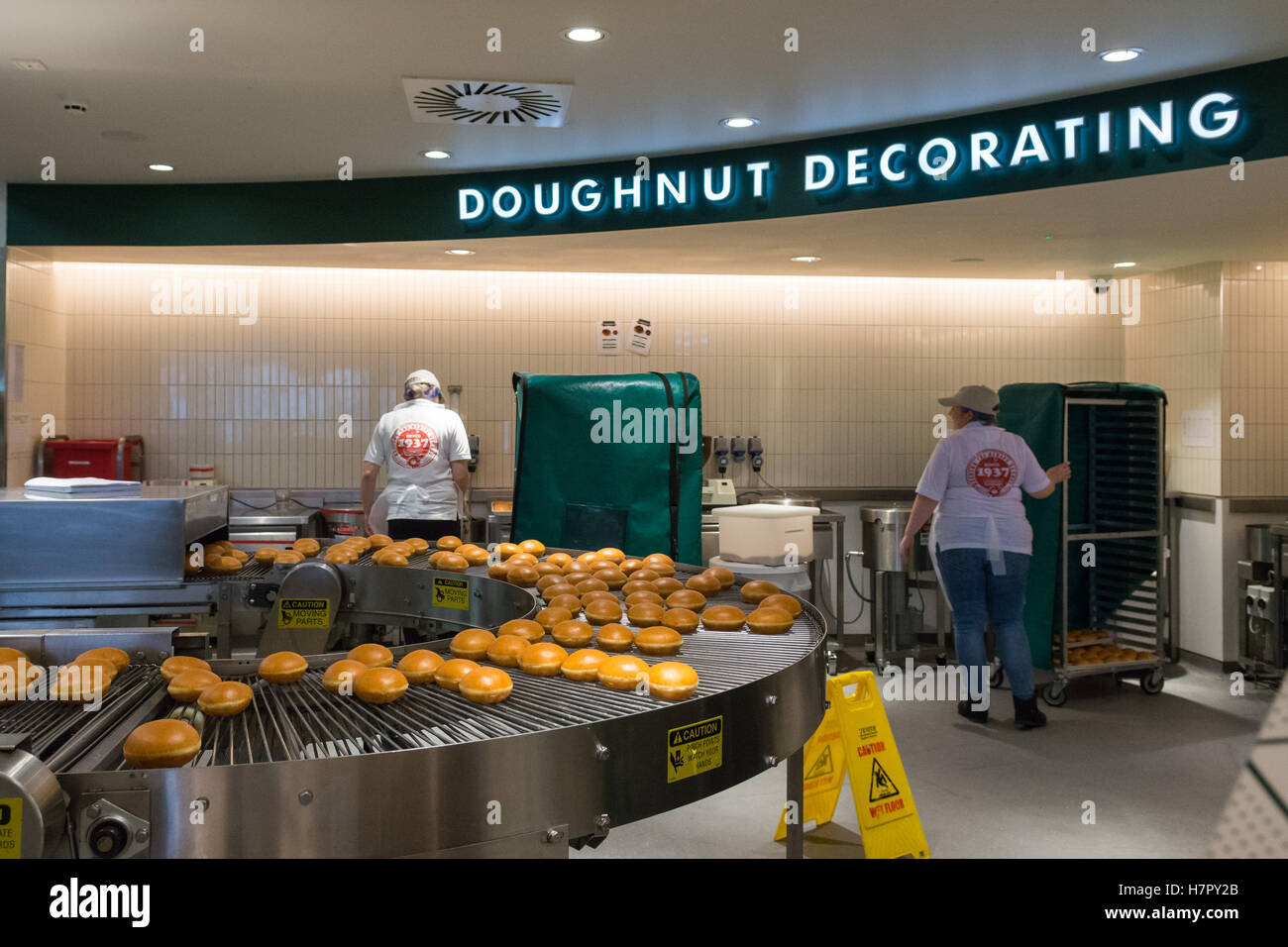 Krispy Kreme Doughnuts Doughnut theatre and Doughnut Decorating window and production line at INTU Braehead, Glasgow, - Stock Image
