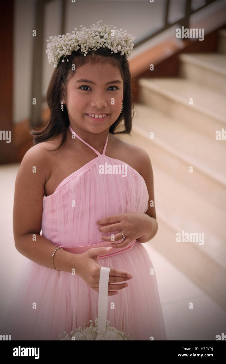 PUERTO PRINCESA,PHILIPPINES-OCTOBER 18,2016: Little bridesmaid poses for the photographer at the wedding of his - Stock Image
