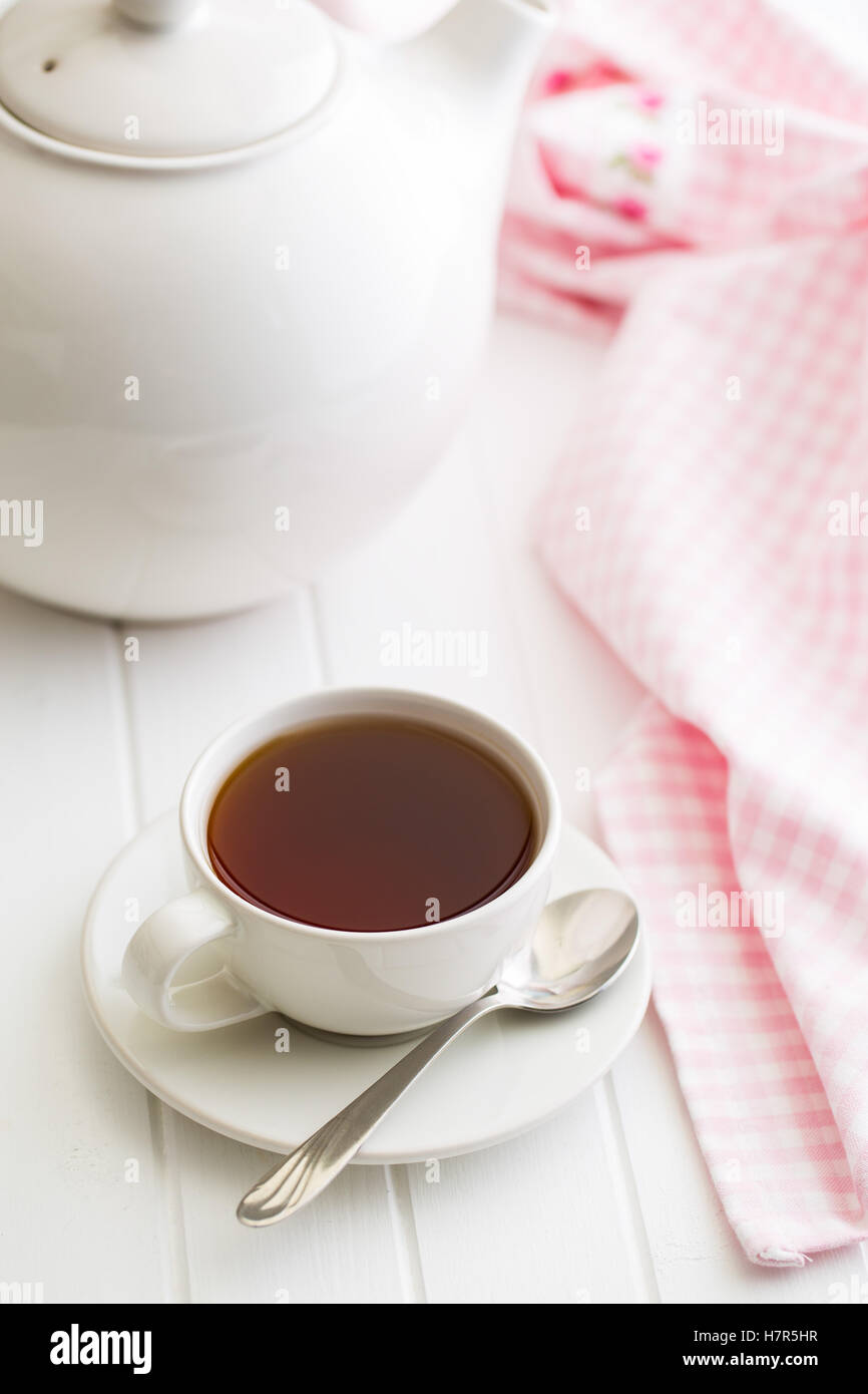 A cup of black tea and teapot on white table. - Stock Image