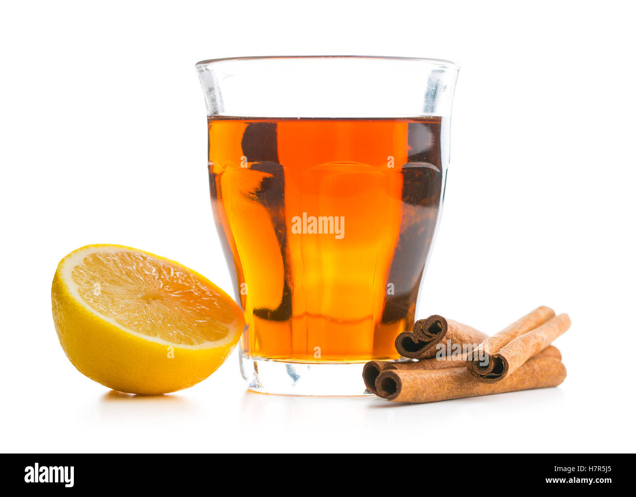 Tea in glass cup, lemon and cinnamon sticks isolated on white background. Stock Photo