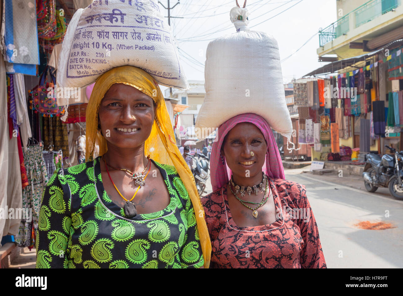 Two women carrying sacks of rice or flour on their heads in the traditional Indian manner, Pushkar, India - Stock Image