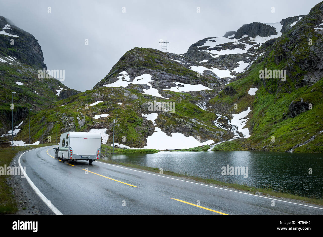 Camper traveling at scenic norwegian road in the mountains. - Stock Image