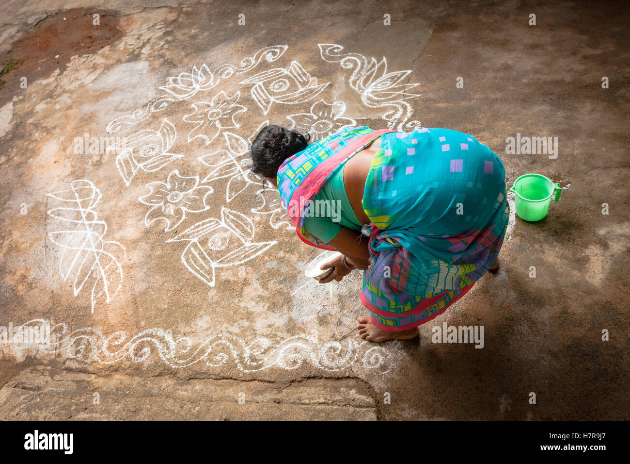 A woman makes a Rangoli drawing on the pavement outside her house, Hospet, south India - Stock Image