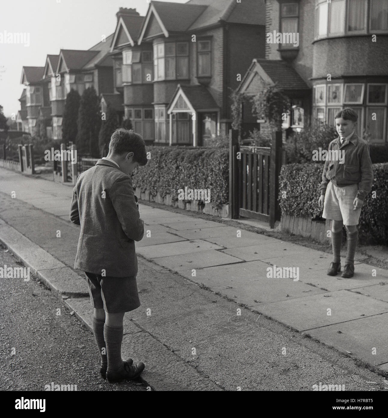1950sm, historical, learning about photography. a young boy in school uniform taking a photograph of his friend - Stock Image