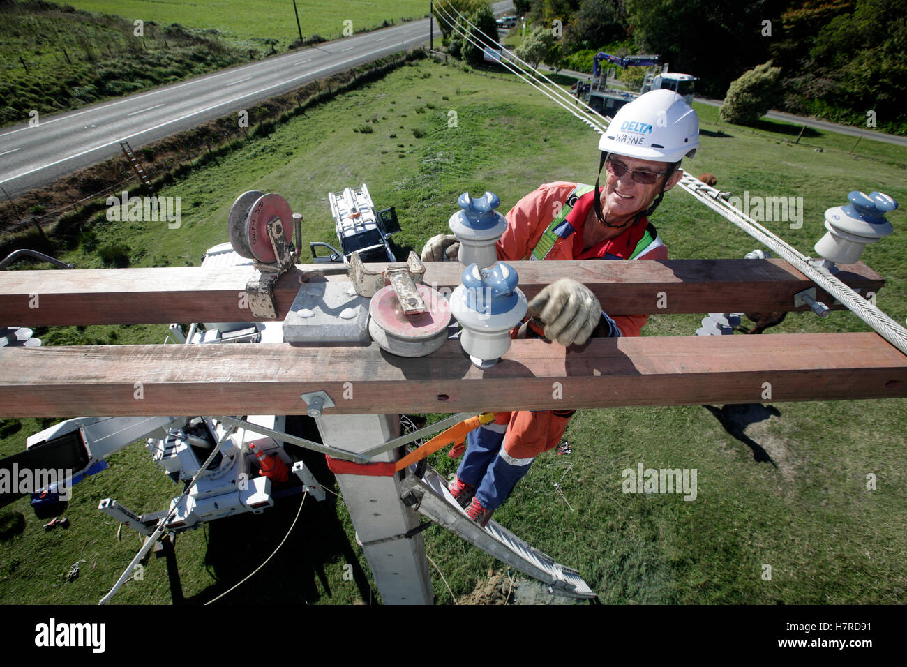 power company worker on ladder replacing high voltage power cables - Stock Image