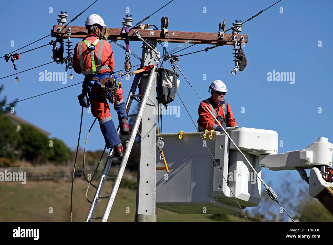 power company workers on ladder and in a cherry picker hoist replacing high voltage power cables - Stock Image