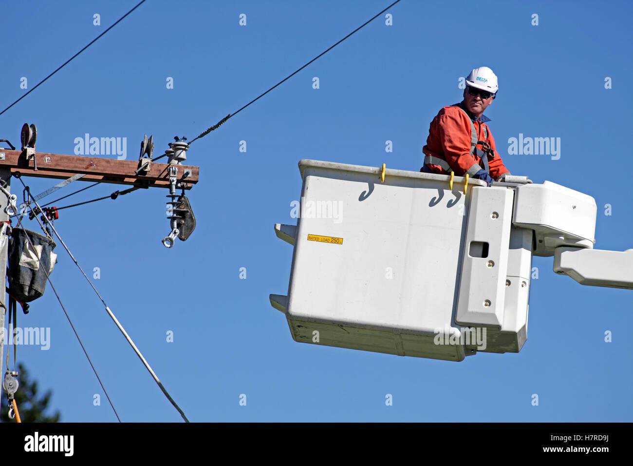 power company worker in a cherry picker hoist replacing high voltage power cables - Stock Image